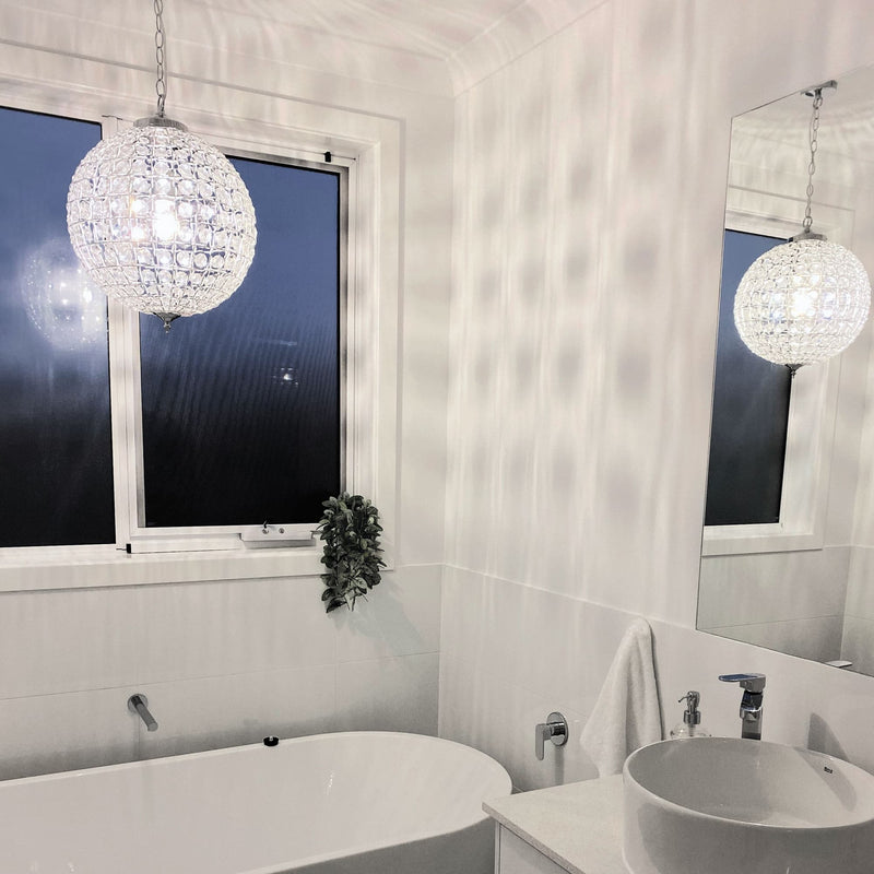 round pendant light with glass crystals hanging in a white bathroom
