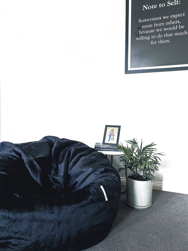 extra large black Pierre fur beanbag next to a palm plant on the floor