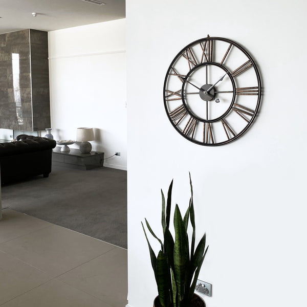 large black bronze metal wall clock on a white wall in a modern living room