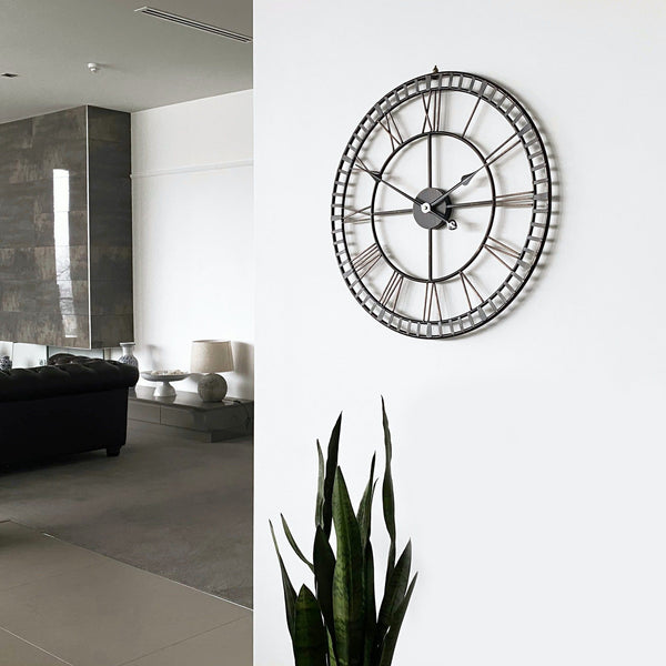 provincial look distressed metal wall clock on a white wall in a modern living room