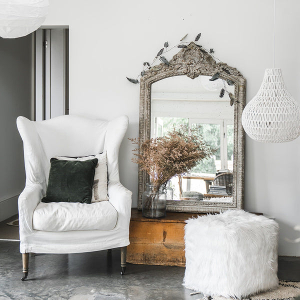 luxe faux fur lush pouf ottoman styled in a Hamptons home with an antique mirror and a rope pendant