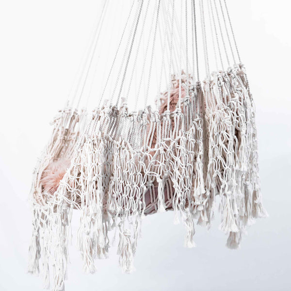 macrame hammock chair with tassels and wooden rod and pink fluffy cushions