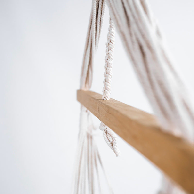 closeup of a macrame hammock chair with tassels and wooden rod