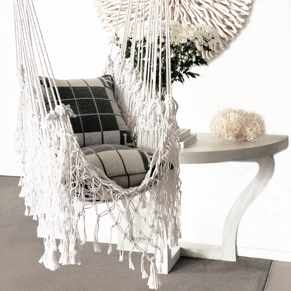 handmade macrame hammock with hermes cushions and flowers on a table