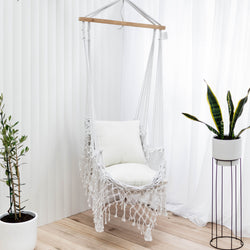 macrame hammock chair with tassels and wooden rod and pink fluffy cushions with a wooden floor under