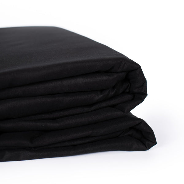 beautiful and soft black folded sheet set with pillowcases on a white background