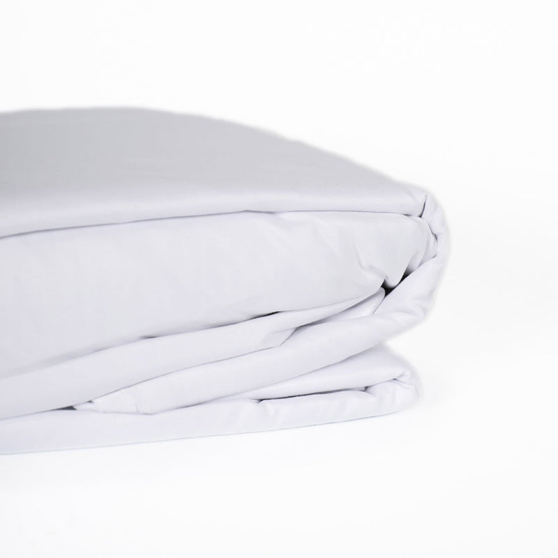 beautiful and soft white folded sheet set with pillowcases on a white background