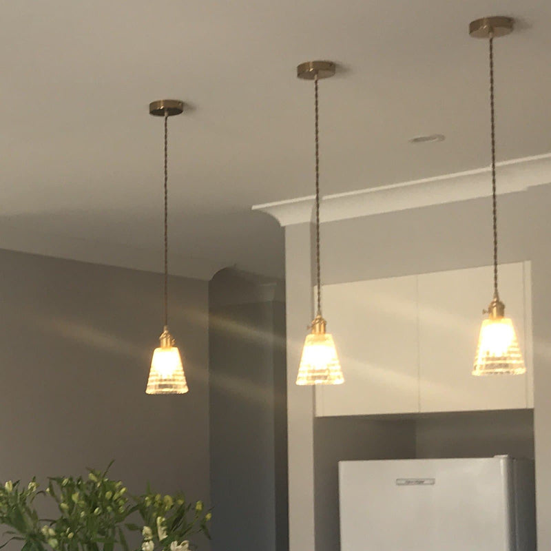 glass pendant light with gold hardware and textured tapered glass shade over a kitchen bench