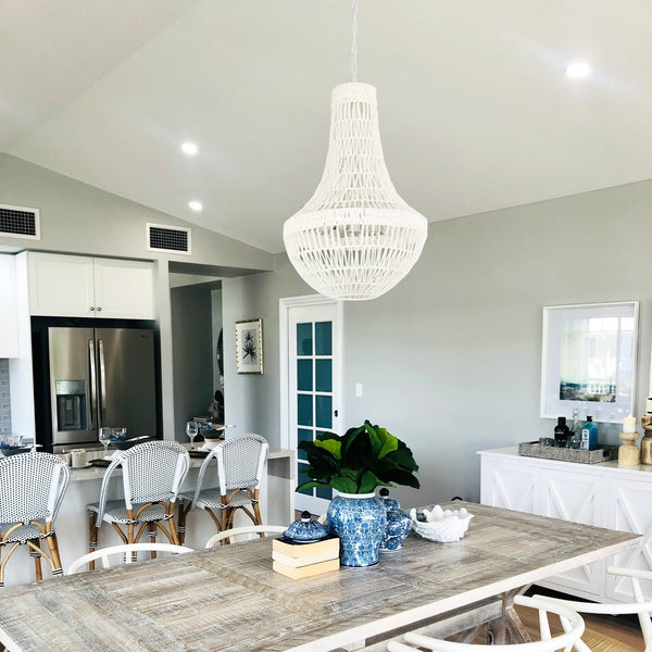 white rope pendant light hanging in a kitchen with white rattan bar stools and a white hampton buffet