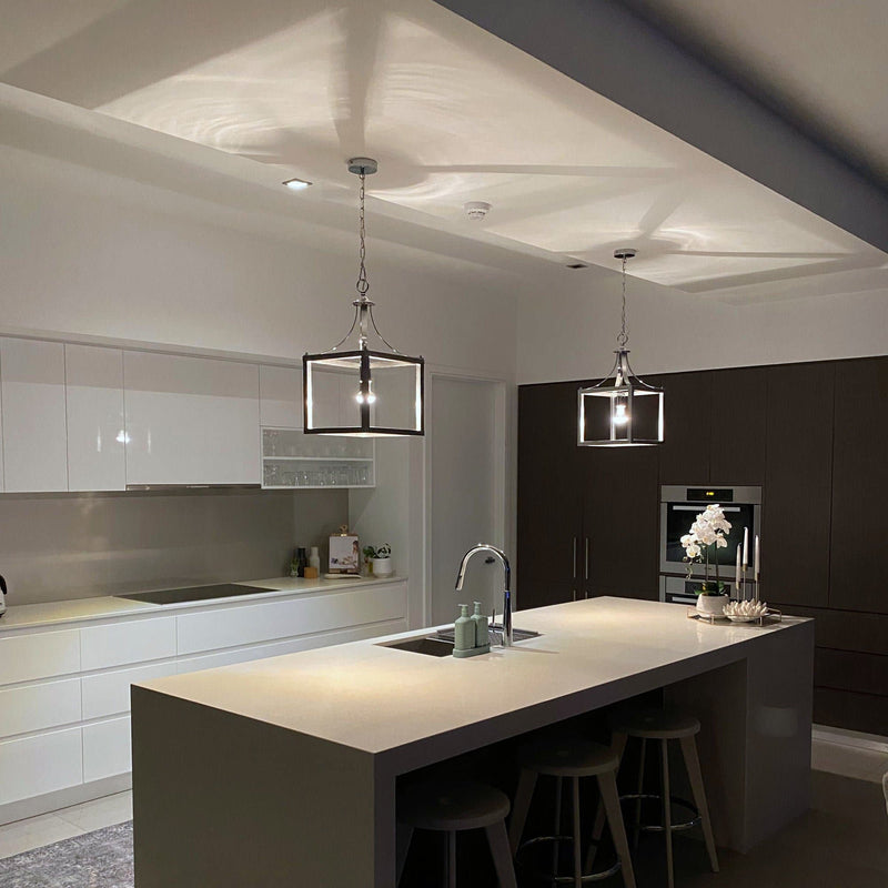 box pendant light in a white kitchen at night time with the lights on