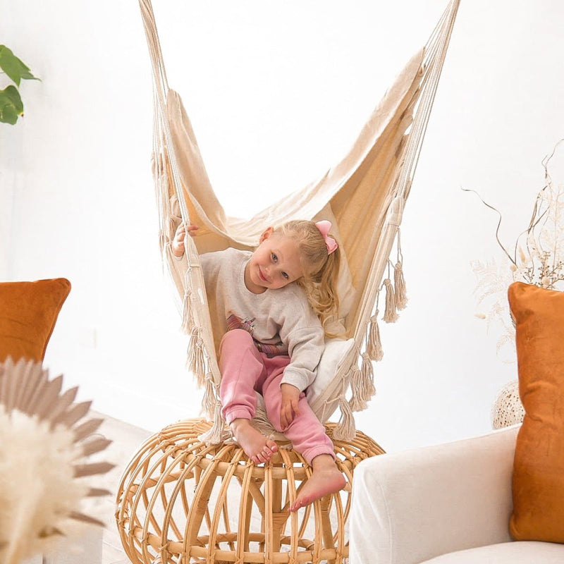 cute girl sitting in a cream soho hanging hammock chair with tassels over a cane side table and orange velvet cushions