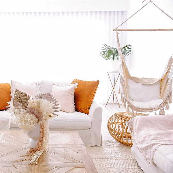 cream hammock hanging in a modern living room with orange cushions and cane side table