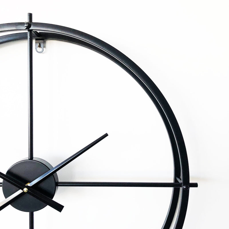 modern matt black metal wall clock on a white background