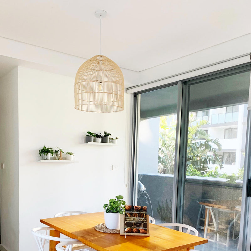 large 45cm rattan pendant hanging in a dining room with plants and white dining chairs