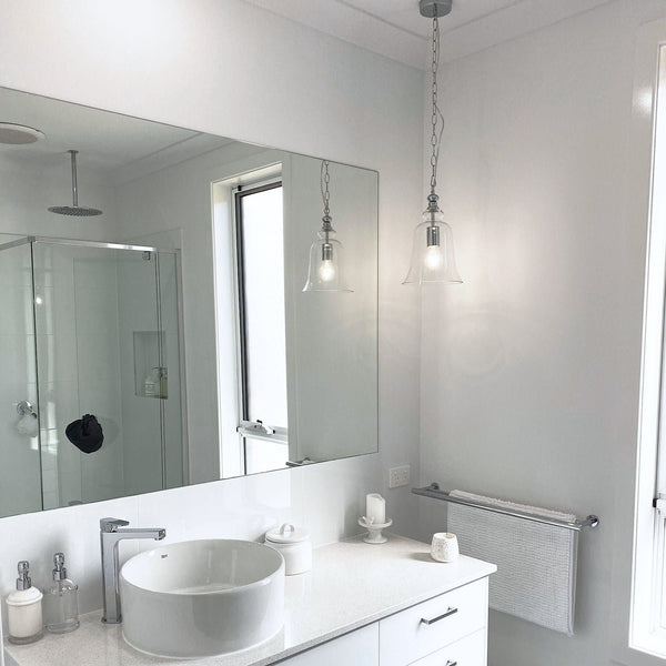 chrome pendant light hanging in a white bathroom