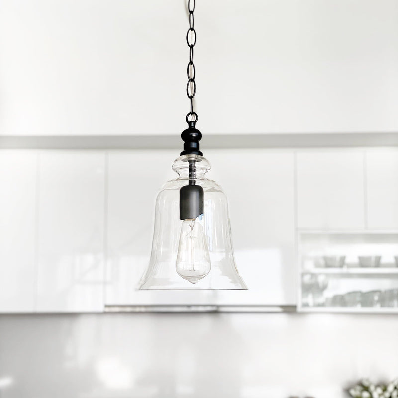 glass pendant light in a bell shape with black hardware hanging over a kitchen bench