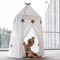 pretty girl playing in a white castle play tent with stars and moon