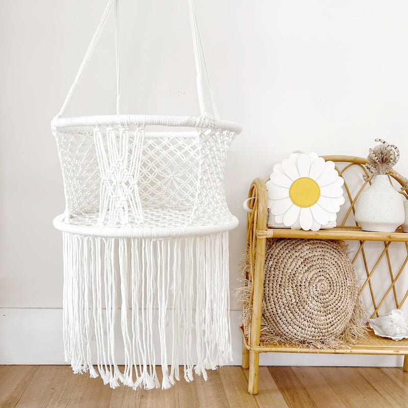 baby swing hammock chair next to a rattan shelf