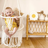 baby sitting in a macrame swing chair with yellow overalls
