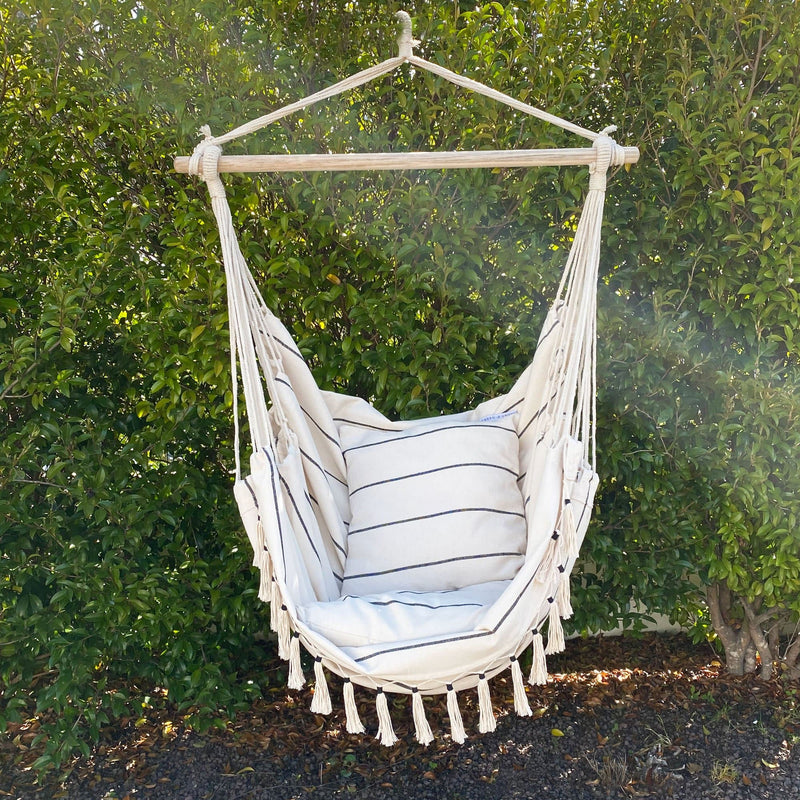 hanging hammock chair with pinstripe pattern and comes with matching cushions hanging out in the garden