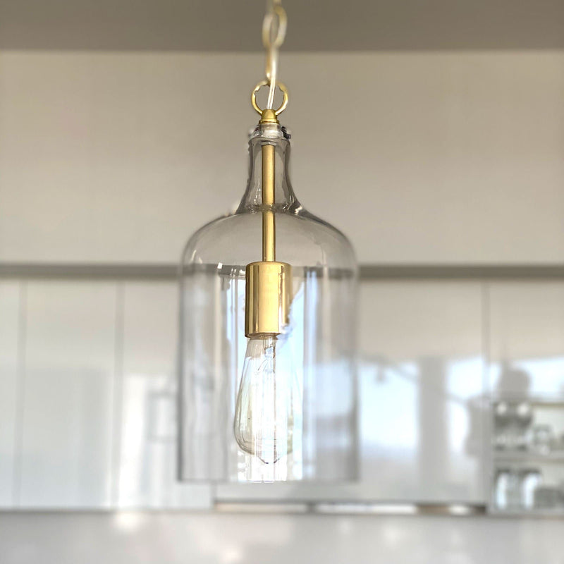kendal glass pendant light with gold hardware hanging in a white kitchen