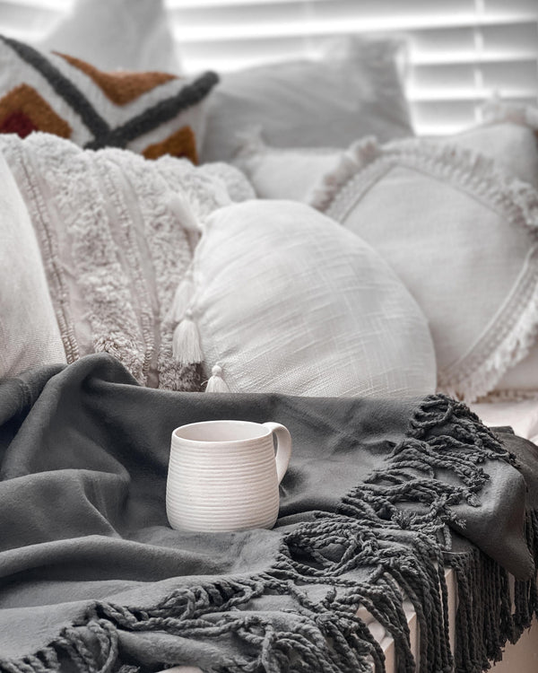 luxury bamboo blanket throw on a couch with natural cushions and a stoneware cup