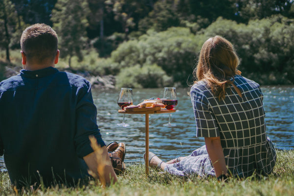 couple sitting by the river enjoying a wine and cheese platter on a bamboo picnic table