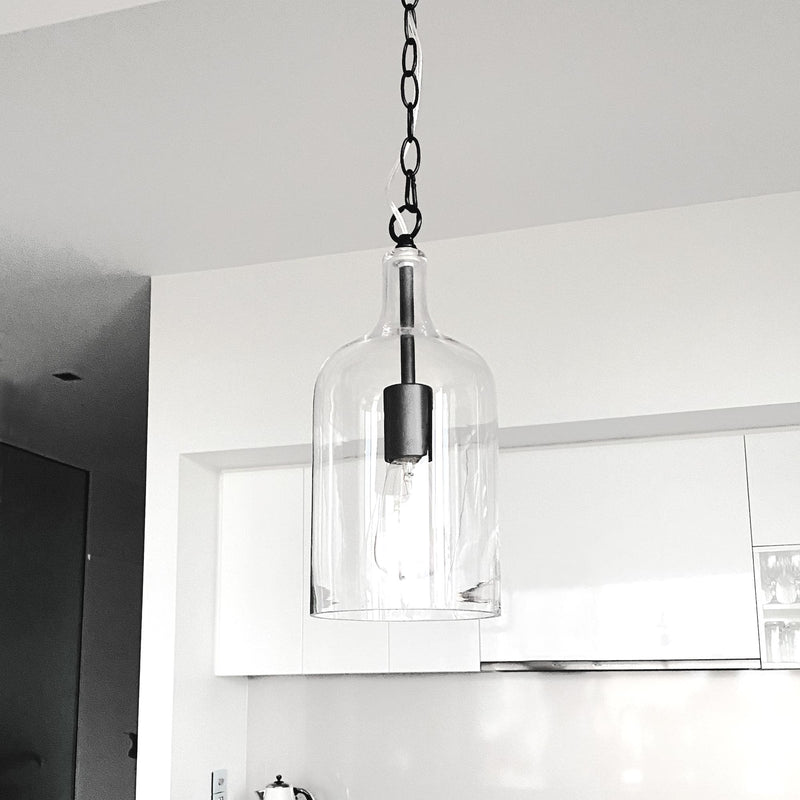 glass pendant light with black hardware and adjustable chain hanging  in a white kitchen