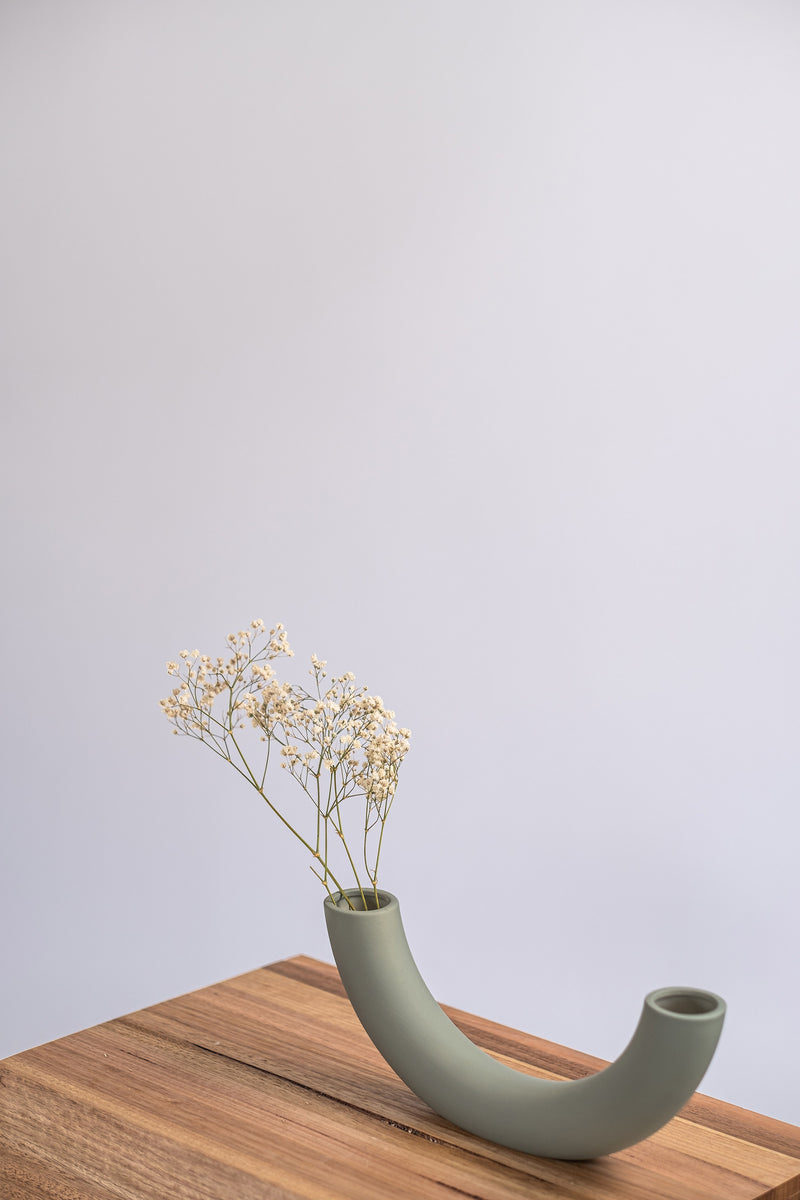 modern sage ceramic vase on a wooden shelf with dried flowers