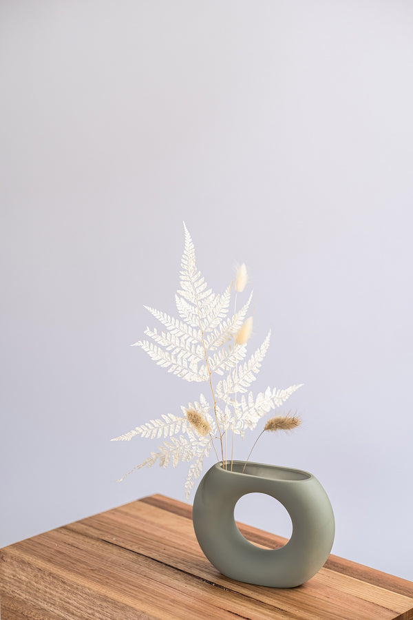 modern sage ceramic vase on a wooden shelf with dried leaves