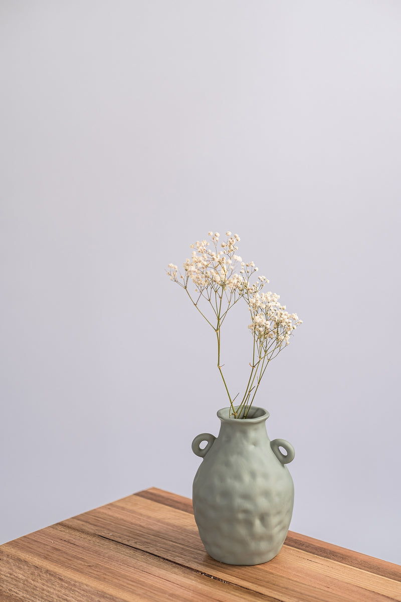 sage ceramic vase on a wooden shelf with dried flowers
