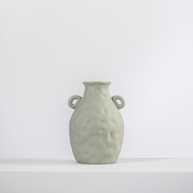 sage ceramic vase on a white shelf