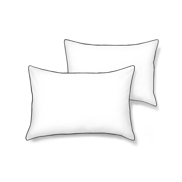white pillowcase set with black piping on a white background