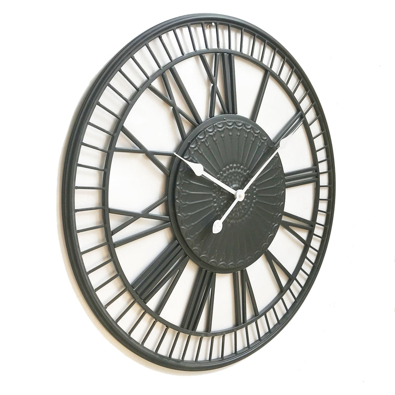 large metal wall clock with white hands on a white background