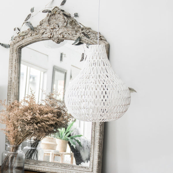 white rope pendant light hanging by an antique mirror