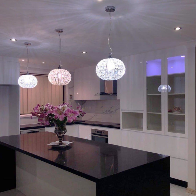 3 lily round crystal pendant lights with chrome fittings over a modern kitchen bench
