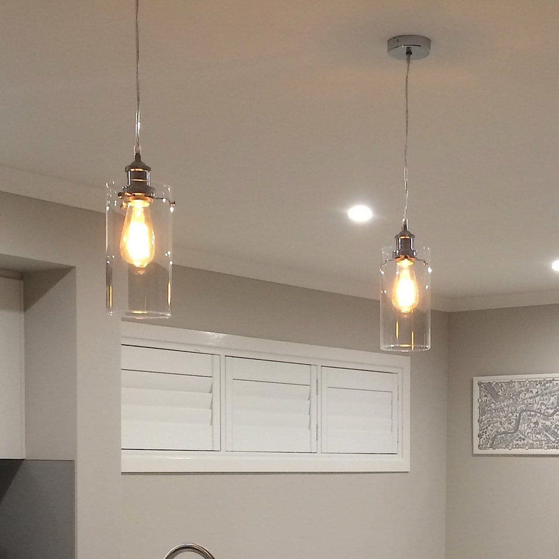 lifestyle of 2 allira glass pendant lights hanging in a kitchen with the lights on