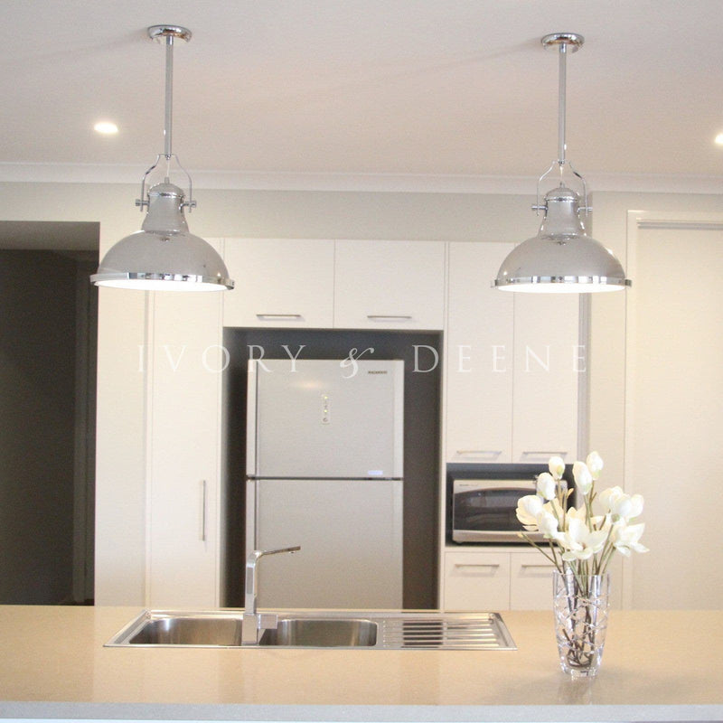 chrome industrial pendant lights hanging over a white marble kitchen bench