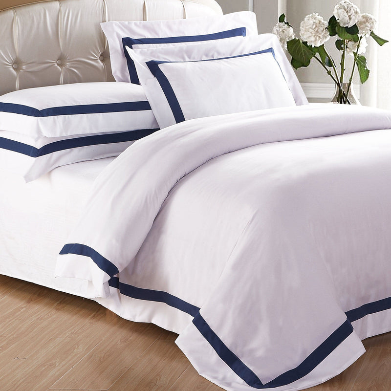 AVA COLLECTION White Quilt Cover Set with Luxury Navy Trim on a quilted bedhead and flowers in a vase