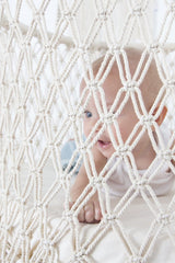 baby in a white macrame bassinet crib suitable to use with a dockatot