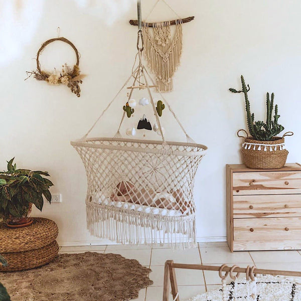 macrame baby hammock bed hanging in a nursery photo by river.and.wood