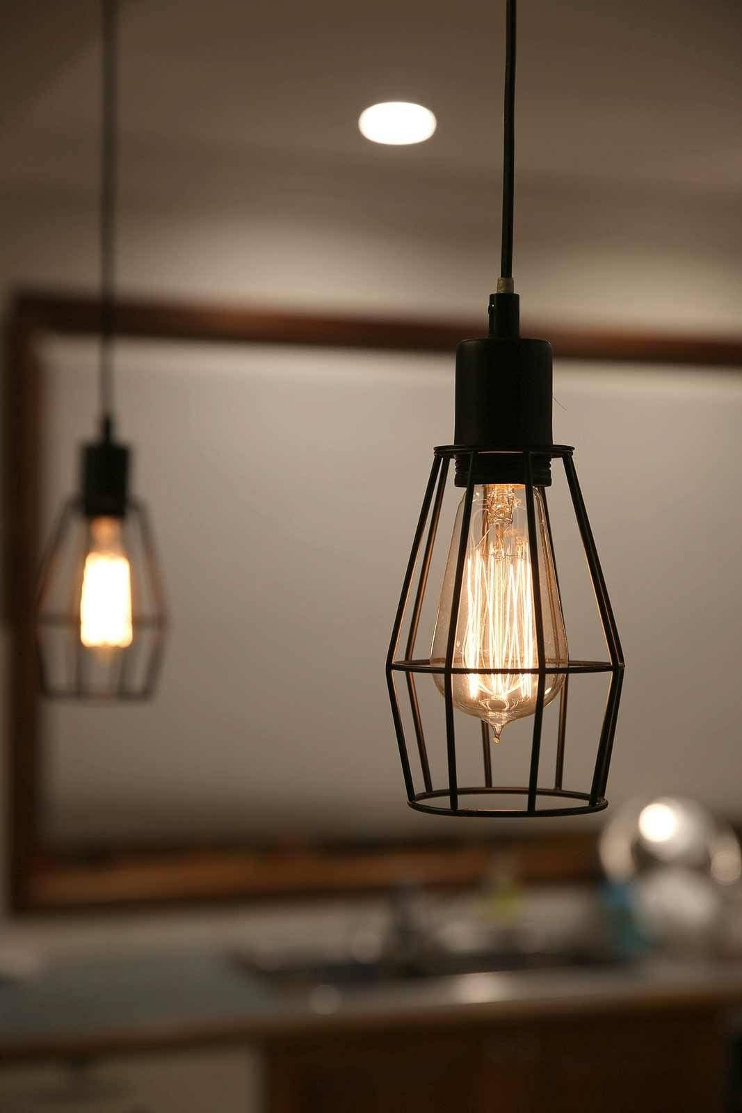 Black Wire Cage Pendant Light Hanging Over A Kitchen Bench