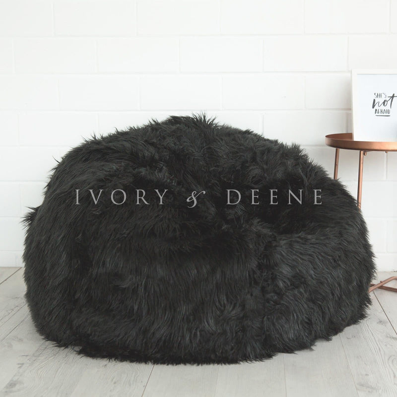 black lush fur beanbag with copper table and book