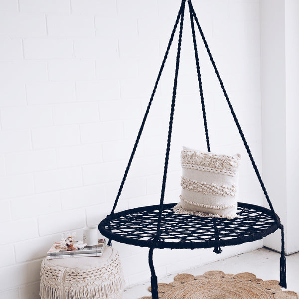 round nest swing made of macrame with cream cushion