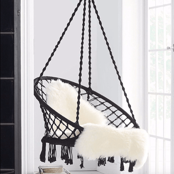 black macrame hammock swing chair with white sheepskin