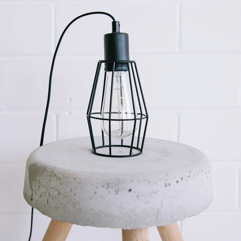 black wire pendant light on a concrete stool with wooden legs