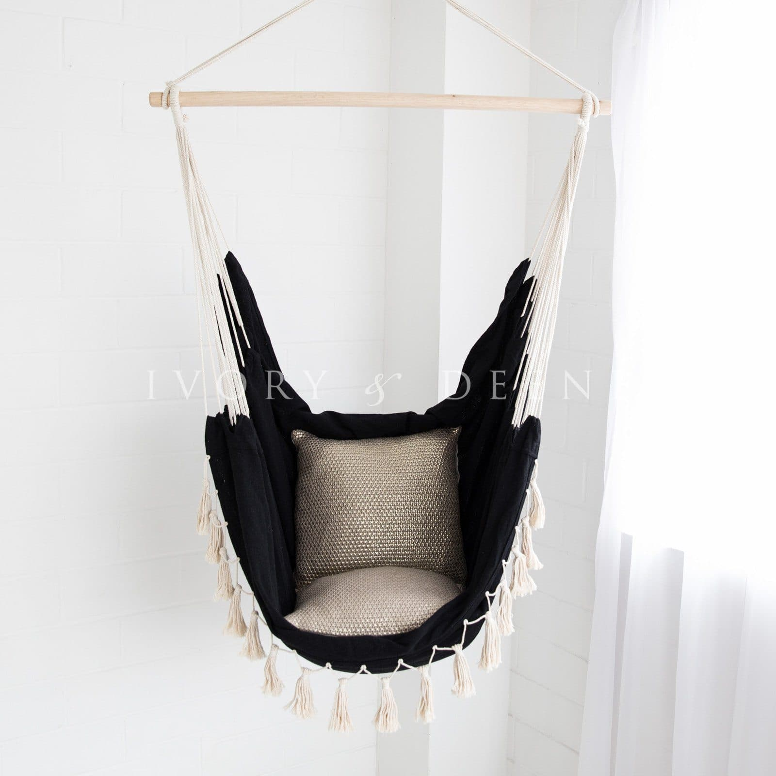 black hammock with cream tassels and gold metallic cushions on white background