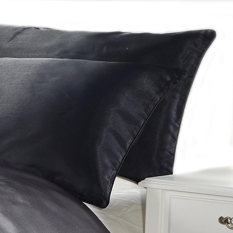 black satin silk feel pillowcase set on a bed with white background
