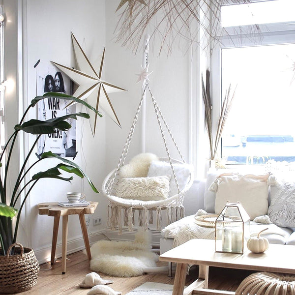 macrame hammock chair hanging in a living room with cushions, plants and furs