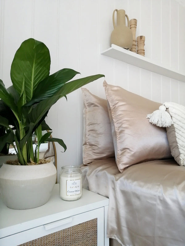 gorgeous champagne satin quilt cover in a white bedroom with plants, candles and floating shelf